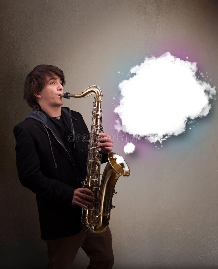 使用在有拷贝空间的萨克斯管的年轻人在白色云彩 免版税库存照片