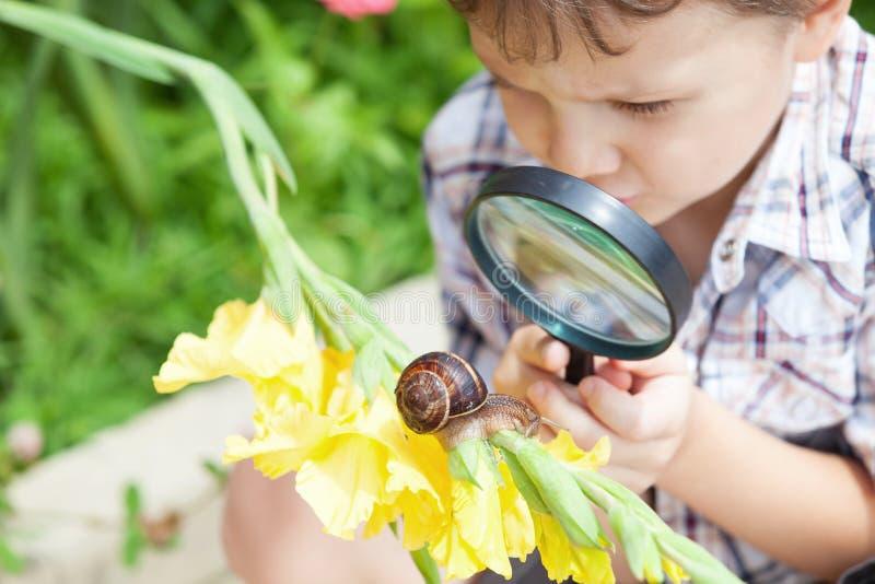 使用在有蜗牛的公园的愉快的小男孩在天时间 免版税图库摄影