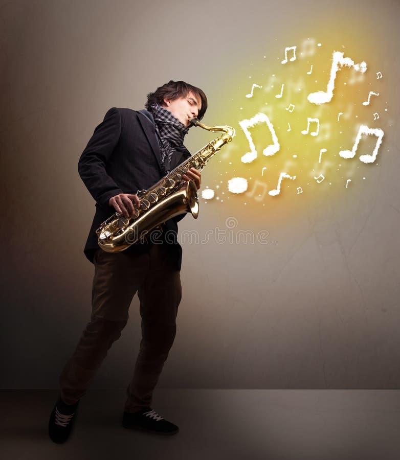 使用在有音符的萨克斯管的英俊的音乐家 库存照片