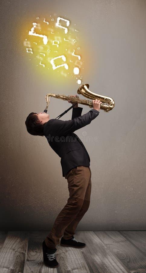 使用在有音符的萨克斯管的英俊的音乐家 图库摄影