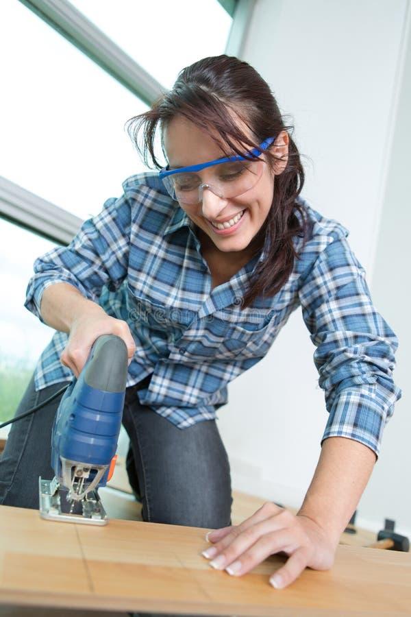 使用在木头的年轻女性木匠带锯在车间 免版税库存照片