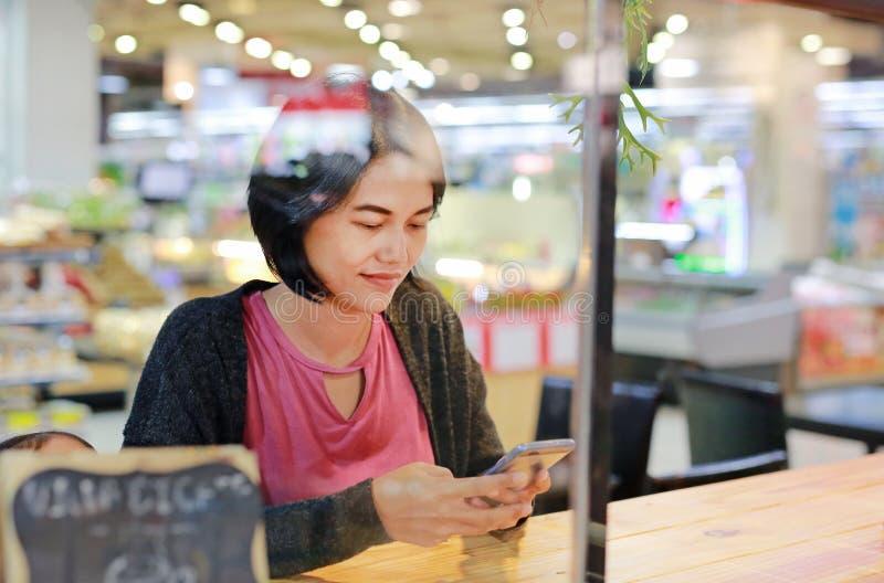 使用在柜台的愉快的亚裔妇女画象智能手机在有玻璃窗反射的超级市场 免版税库存照片