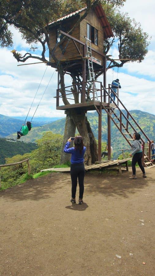 使用在树上小屋的摇摆的游人近城市 Banos位于通古拉瓦火山volc的北山麓小丘 库存照片