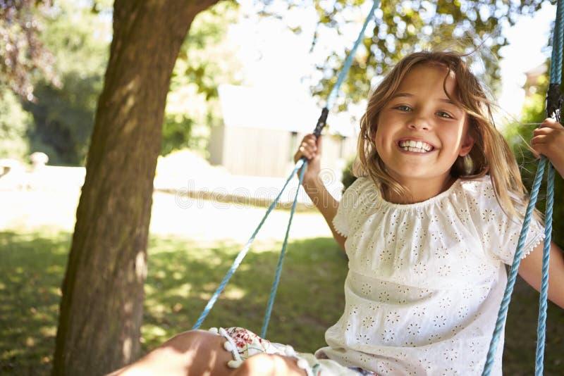 使用在树摇摆的女孩画象 免版税库存照片