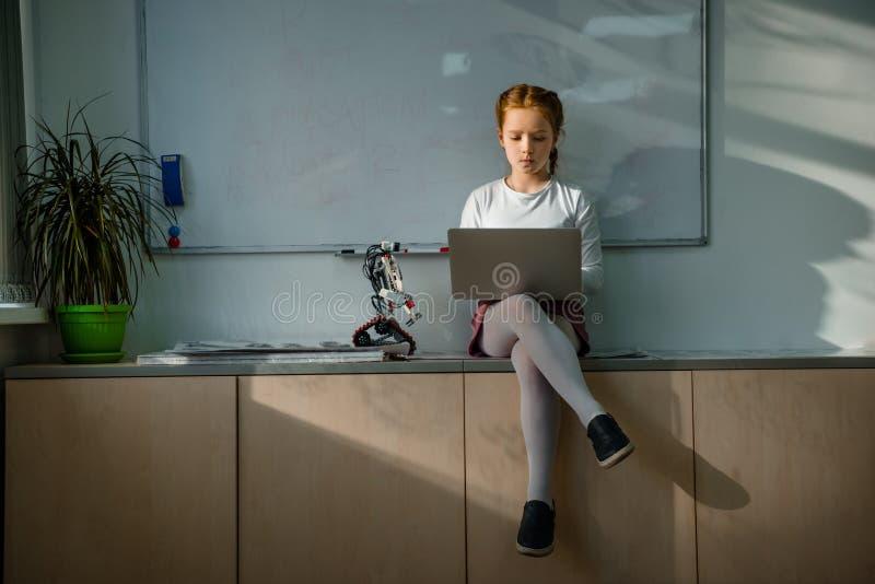 使用在桌上的小女小学生膝上型计算机在教室 免版税库存图片