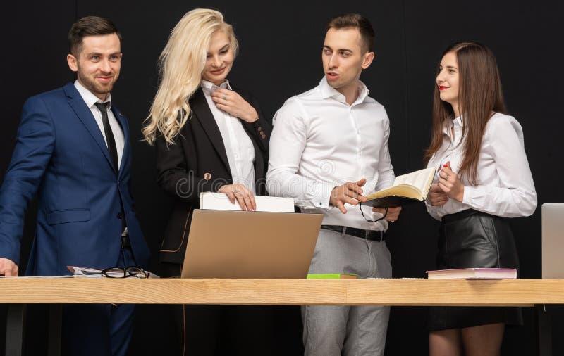使用在桌上的膝上型计算机友好的bisiness队有工作在办公室 免版税库存图片