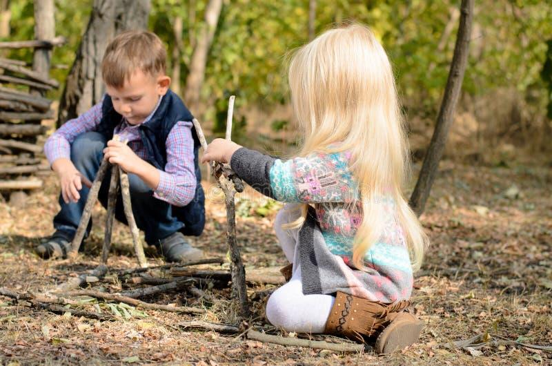 使用在森林的小男孩和女孩用棍子 免版税库存图片