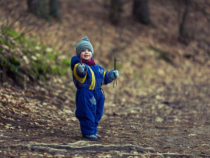 使用在森林里的小白种人男孩在早期的春天 免版税图库摄影