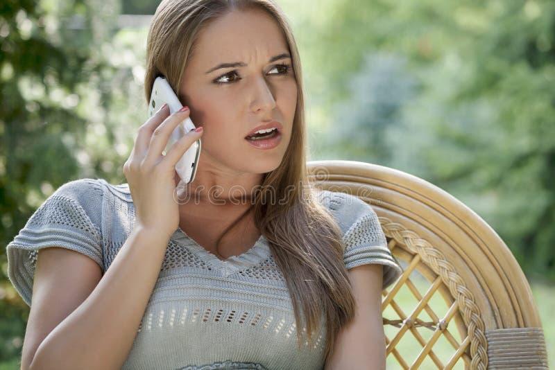 使用在椅子的严肃的少妇手机在公园 免版税库存照片