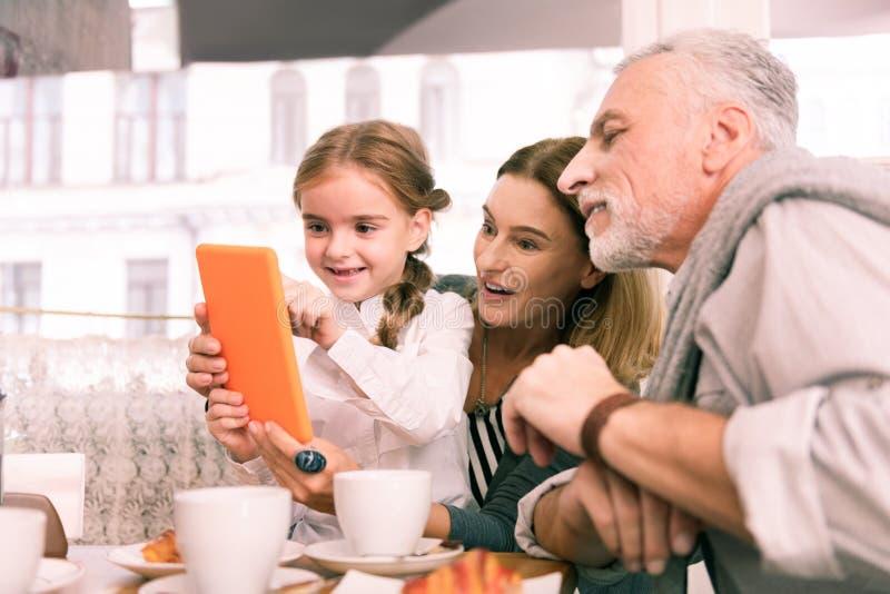 使用在橙色片剂的孙女坐在祖父母附近 免版税库存图片