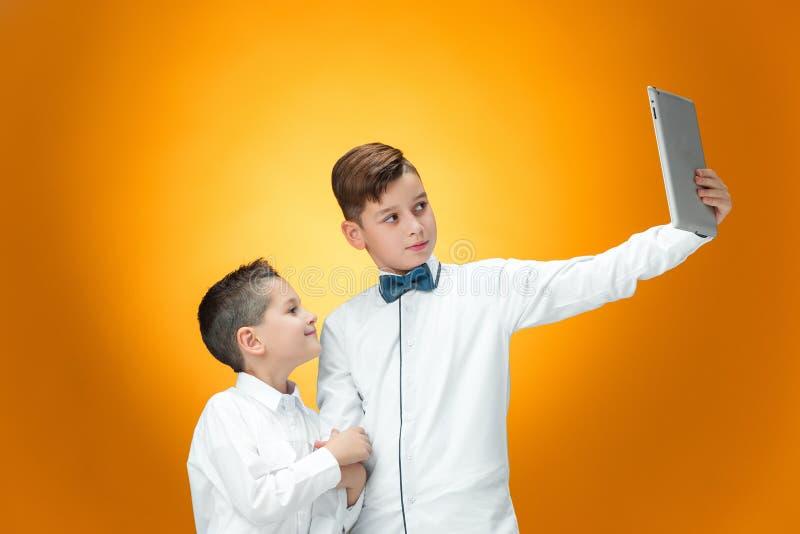 使用在橙色背景的两个男孩膝上型计算机 库存图片
