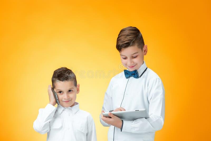 使用在橙色背景的两个男孩膝上型计算机 库存照片