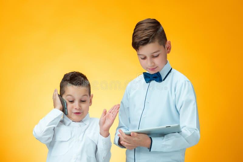 使用在橙色背景的两个男孩膝上型计算机 免版税库存图片