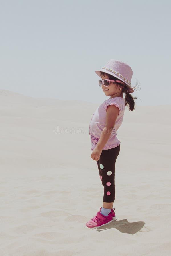 使用在沙丘的逗人喜爱的女孩 库存照片