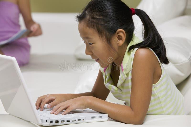 使用在沙发关闭的女孩膝上型计算机侧视图 免版税库存照片