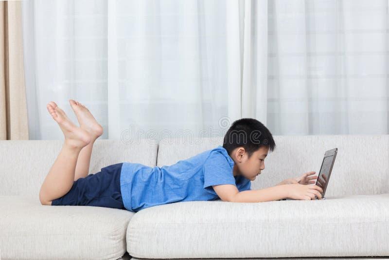使用在沙发的亚裔中国小男孩膝上型计算机 免版税库存图片