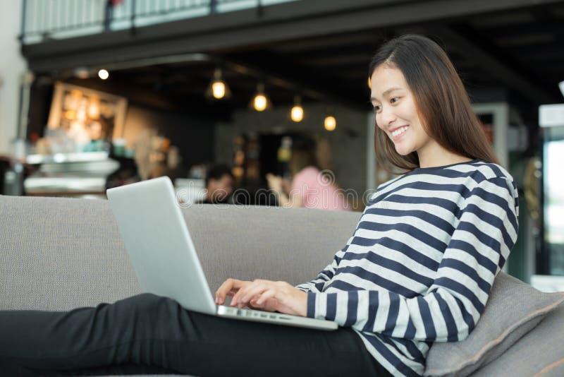 使用在沙发的亚裔妇女笔记本在咖啡店,独立wo 免版税库存图片