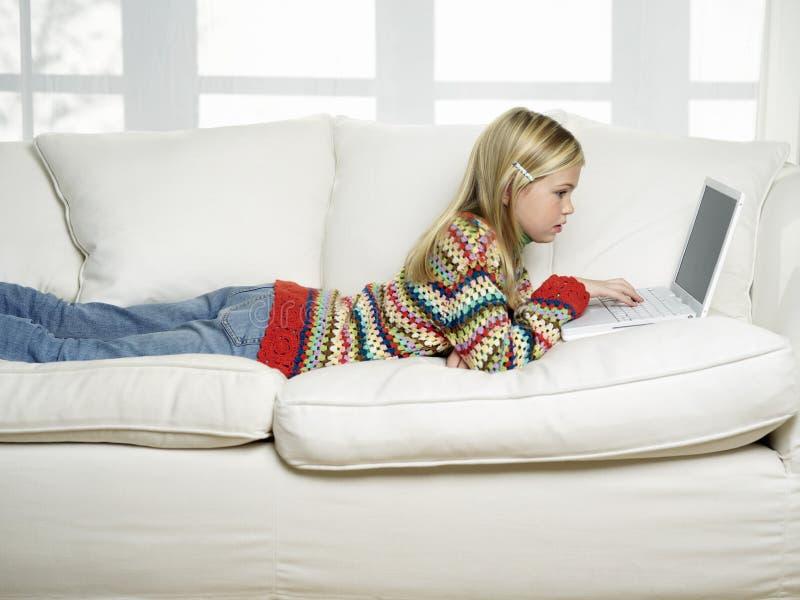 使用在沙发的女孩膝上型计算机  免版税图库摄影