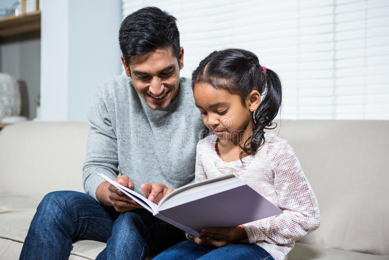 使用在沙发的愉快的父亲和女儿膝上型计算机 免版税库存图片