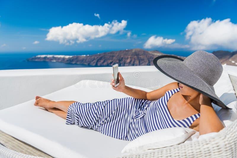 使用在沙发的松弛妇女巧妙的电话在手段 免版税库存照片