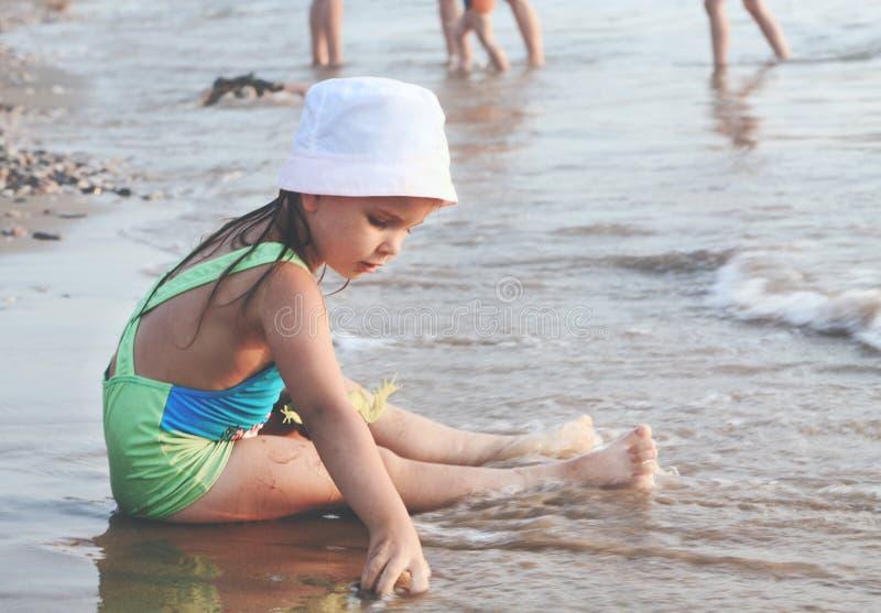 使用在沙子海滩的一个小逗人喜爱的女孩 免版税图库摄影