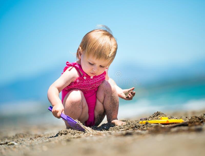 使用在沙子的小逗人喜爱的女孩 免版税库存照片