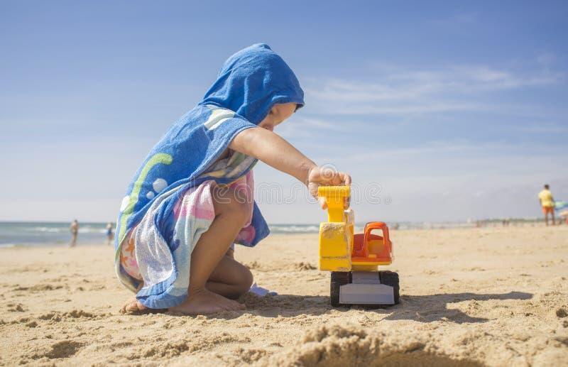 使用在沙子的男婴在与挖掘机玩具的海滩 免版税库存照片