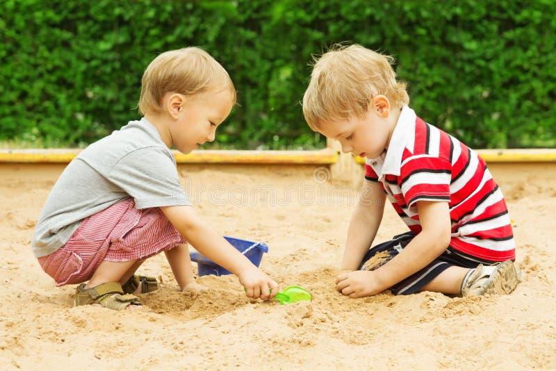 使用在沙子,两个在沙盒的儿童男孩室外休闲的孩子 免版税库存图片