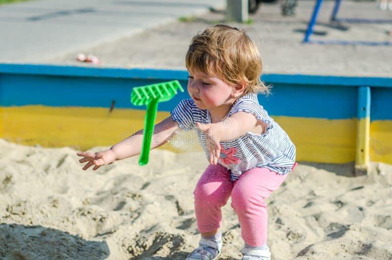 Download 使用在沙盒沙子土墩的操场的小迷人的女孩婴孩在有铁锹和犁耙的桶 库存图片 - 图片 包括有 航空, 题头: 72358387