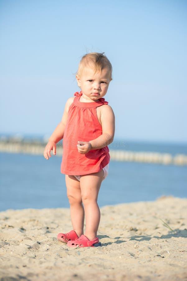 使用在沙滩的红色礼服的女婴在海附近 免版税图库摄影