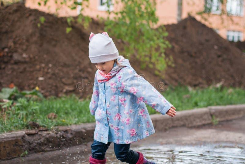 使用在泥泞的水坑的孩子 免版税库存图片