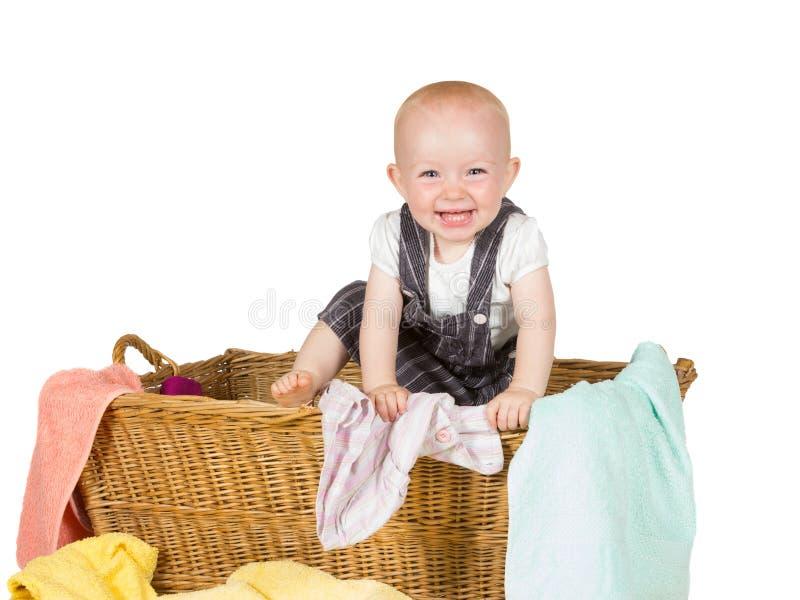 使用在洗衣篮的笑的婴孩 免版税库存图片