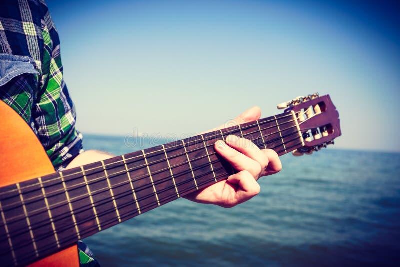 使用在海旁边的吉他弹奏者 免版税库存照片