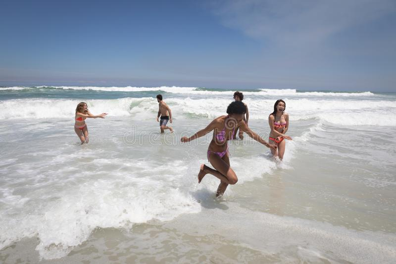 使用在海浪的愉快的小组朋友 图库摄影