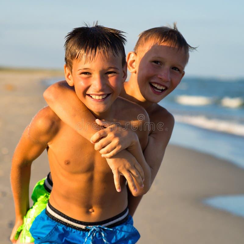 使用在海海滩的两个愉快的少年特写镜头画象  免版税库存照片