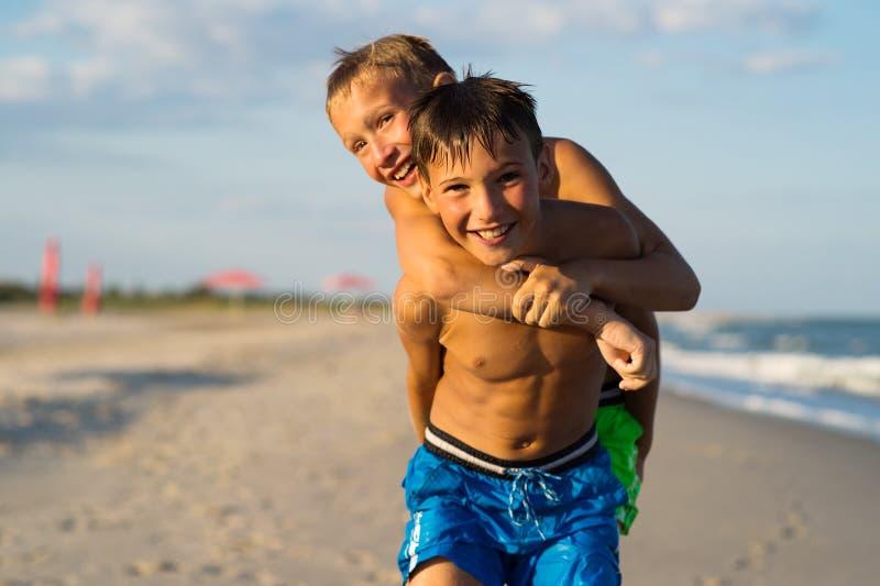 使用在海海滩的两个愉快的少年特写镜头画象  免版税库存图片