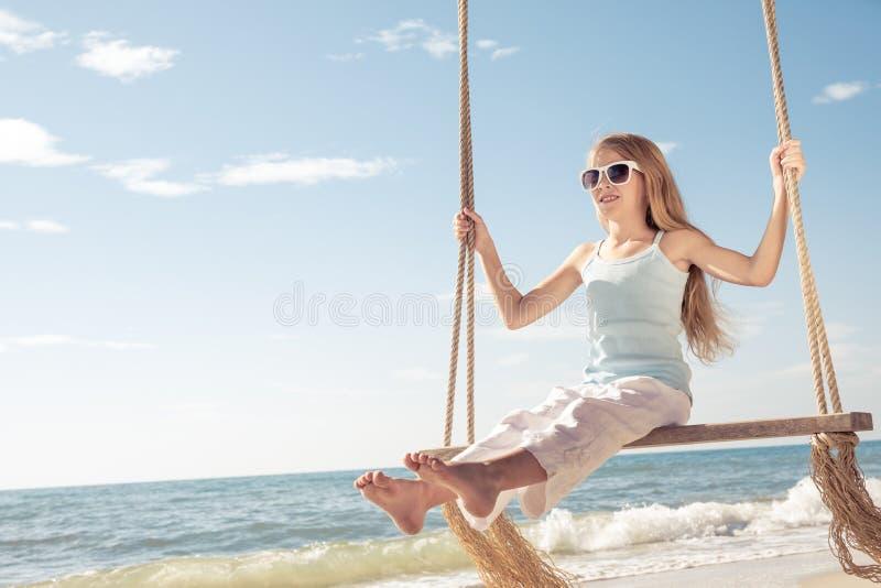 使用在海滩的一个愉快的小女孩在天时间 库存图片