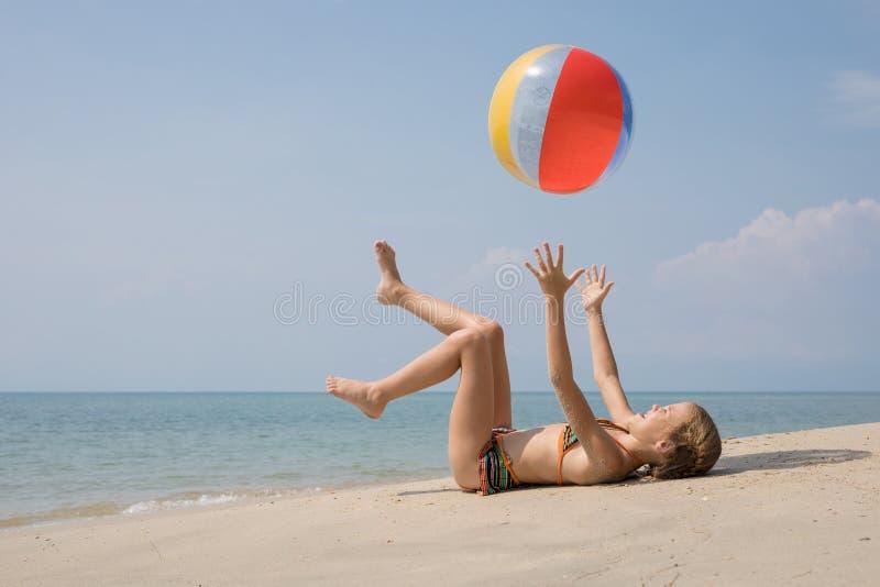 使用在海滩的一愉快的女孩在白天 免版税库存照片