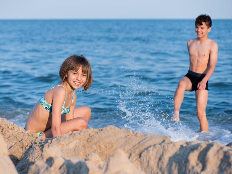 使用在海滩的兄弟和姐妹 免版税库存照片