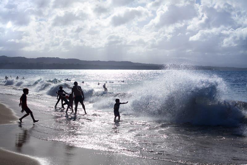 使用在海滩的孩子和人剪影在波浪和水中在度假,蓝色海,波浪太阳光飞溅 库存照片