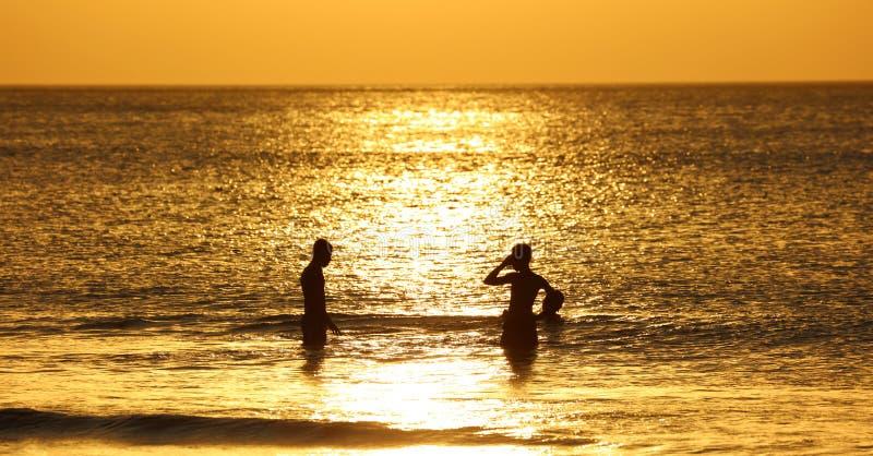 使用在海滩的孩子在巴厘岛,在日落期间的印度尼西亚在海滩 免版税库存照片