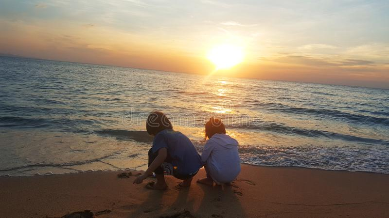 使用在海滩的孩子在日落 海,旅行和假期概念,夏时概念 库存图片