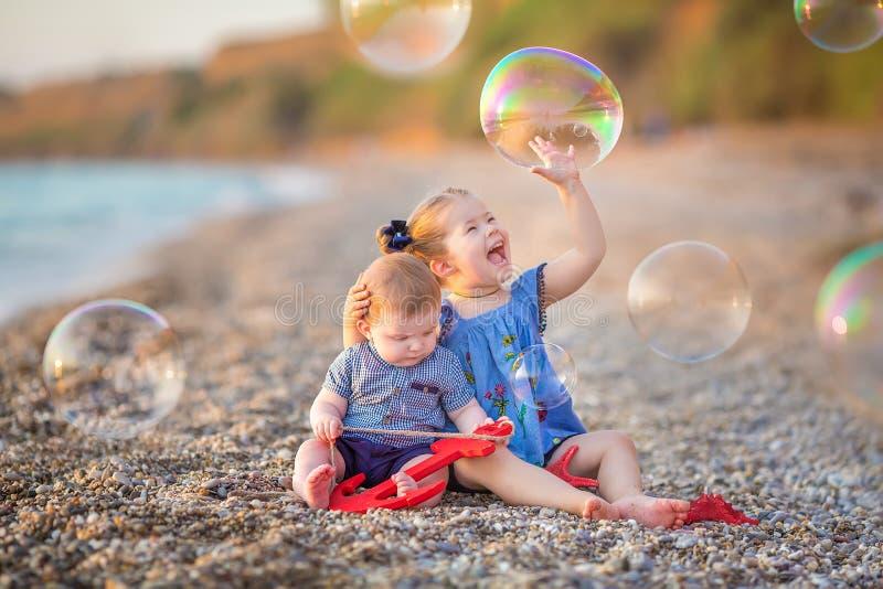 使用在海滩的岸断裂的兄弟和姐妹在与bubles的热的暑假天期间 库存照片