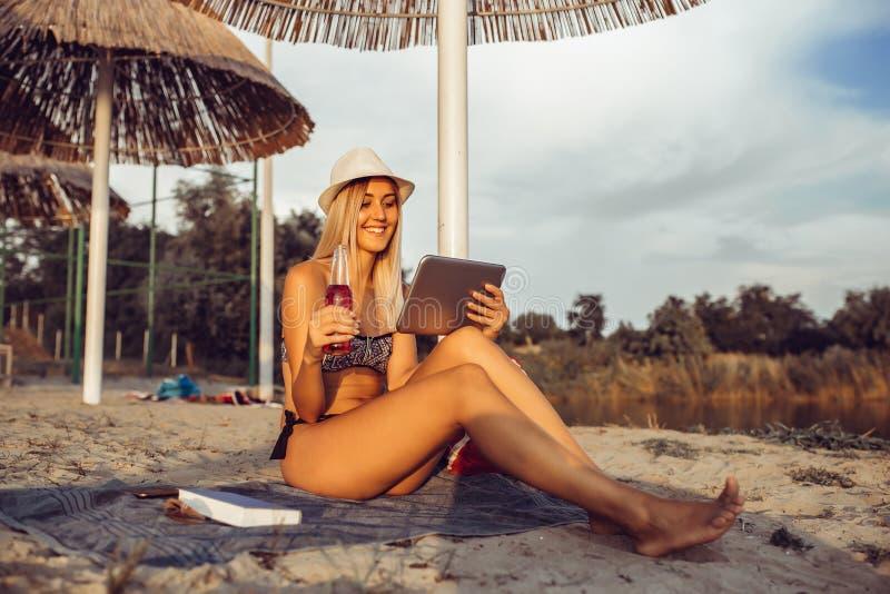 使用在海滩的愉快的女孩片剂 库存照片