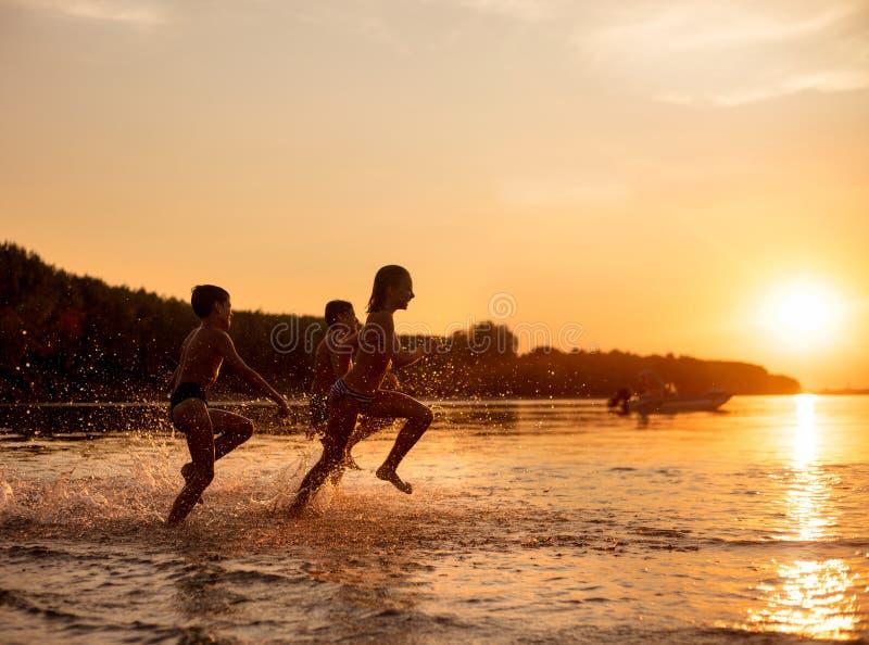 使用在海滩的愉快的孩子在日落时间 免版税库存图片