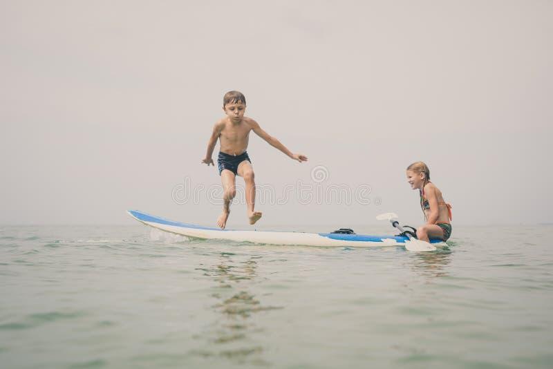 快乐的孩子们白天在沙滩上玩耍 免版税库存照片