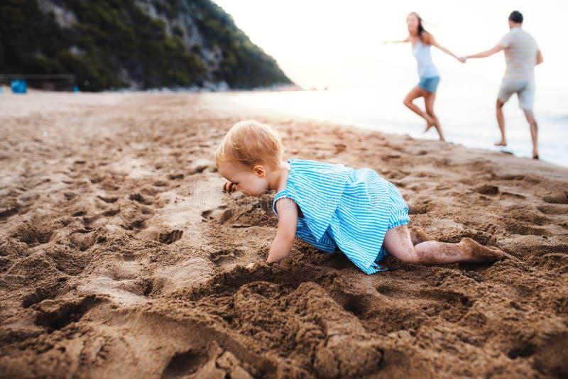 使用在海滩的沙子的一个小小孩女孩在度假夏天休假 免版税图库摄影