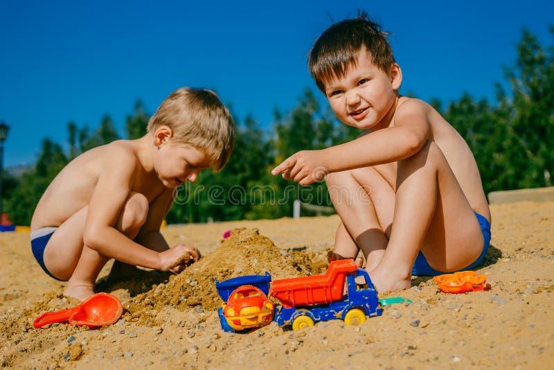 使用在海滩的沙子的两个男孩 免版税库存照片