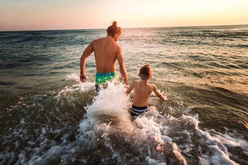 使用在海滩的父亲和儿子 免版税库存照片