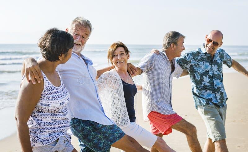 使用在海滩的资深朋友 免版税库存图片